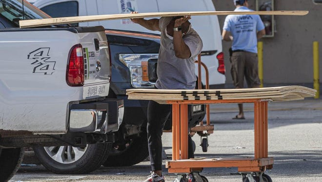 A man loads plywood into the bed of his pickup truck at the Home Depot on Palm Beach Lakes Blvd. Friday in West Palm Beach, in preparation for Hurricane Isaias amking landfall Saturday.