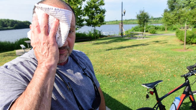 """Arturo Rosario, 68, of Ft. Lee, wipes the sweat away from his face while on his morning bike ride through Overpeck County Park Tuesday morning. Rosario said,  """"I am a hot weather person, as long as I have enough fluids in me, I am good to go."""""""