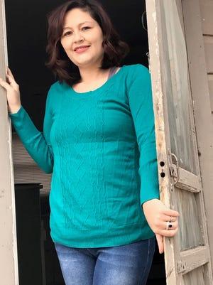 Victoria Gutierrez stands in the doorway of her new apartment.