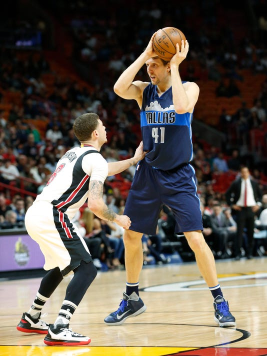 Dallas Mavericks forward Dirk Nowitzki, right, of Germany, looks for an open teammate past Miami Heat guard Tyler Johnson (8) during the first half of an NBA basketball game, Thursday, Jan. 19, 2017, in Miami. (AP Photo/Wilfredo Lee)