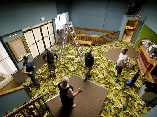 Members of the Help Entertain and Restore Organization take a break last month in their effort to rescue the historic downtown movie theater in Webster City. Residents rallied and held meetings, hashed out volunteer work and launched a fundraising campaign to save the old theater. <137,2014/09/26,Karns/c Russ1><137>