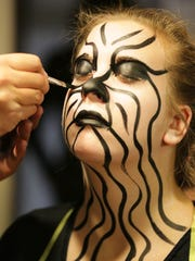 Jessica Ebert has her makeup applied by Ory Green before the evening show on Oct. 10 at the Burial Chamber in Neenah.