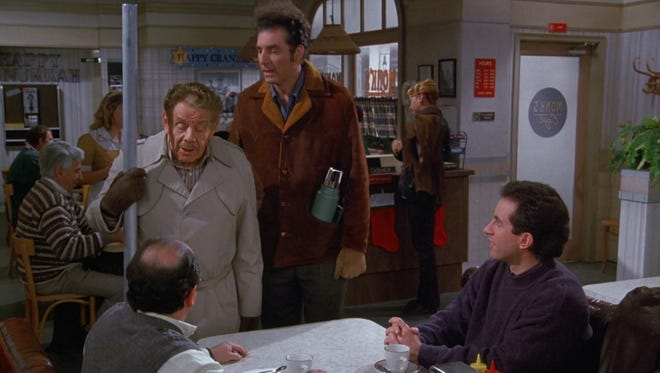 Frank Costanza (Jerry Stiller), with Festivus pole, tries to get son George (Jason Alexander) into the  holiday spirit.