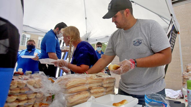 Joshua Flores makes hot dogs for a line of first responders and police officers outside Shelby Police Department on Monday. The lunch giveaway is a part of Flores' Back the Blue One Meal at a Time.