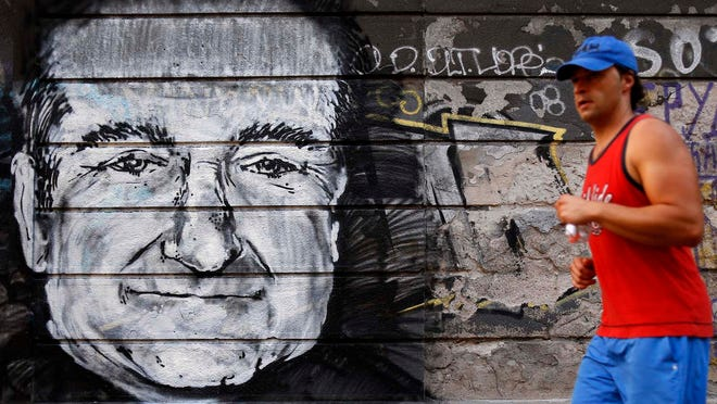 A man runs past a mural on a wall depicting Robin Williams, in Belgrade, Serbia, on Wednesday.
