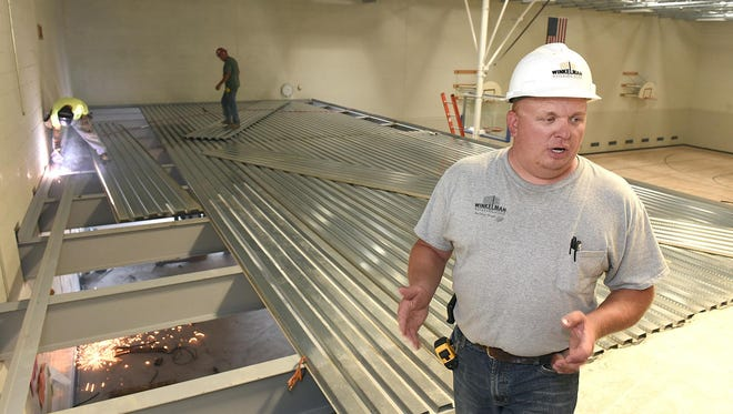 Josh Schwinghammer, project supervisor for Winkelman Builders, shows the steel work Wednesday on decking going in over the old pool which will have a concrete floor and be walled off to create a new band room at North Junior High School.