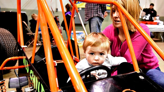 """Billi Jo Lawrence, right, of New Oxford, helps her son Levi Smith, 1, left, into a vehicle in the """"Kid's Zone"""" during the Racing Xtravaganza show at York Expo Center in York on Saturday, Feb. 6, 2016. The 2018 show is set for this coming weekend. (Dawn J. Sagert - The York Dispatch)"""