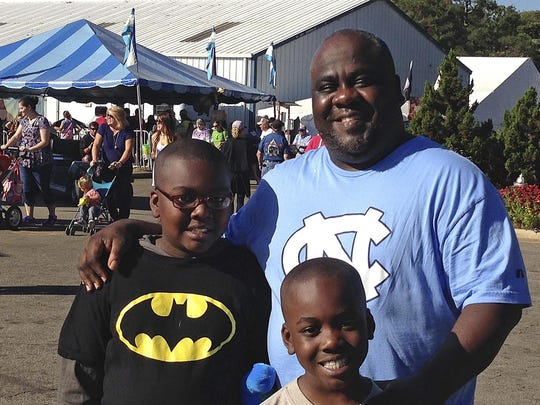 Nicholas Jones, 45, and his sons, 10-year-old son Benjamin (in the Batman shirt) and 7-year-old Christopher take in the sights and sounds of the North Carolina State Fair on Wednesday, Oct. 19, 2016, in Raleigh, N.C. Jones said North Carolina's economy has been disappointing and he doesn't credit Gov. Pat McCrory, who is running for re-election, with leading a comeback. (AP Photo/Emery Dalesio)