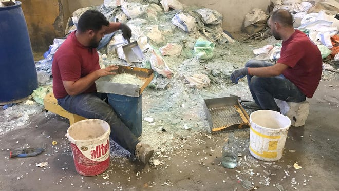 Two workers at a glassware factory in Tripoli, Lebanon, sort through piles of blast-shattered glass.