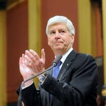 Michigan Governor Rick Snyder applauds members of the military as he  speaks during his State of the State Address on the floor of the House at the Capitol in Lansing tonight.                      t