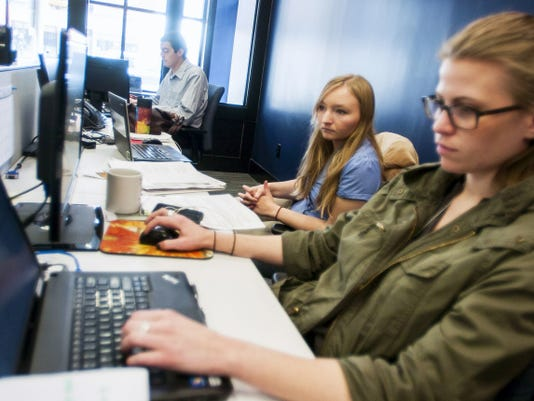 Journalist Jenni Wentz works with assistant metro editor Katy Petiford at the Evening Sun office on 37 Broadway in downtown Hanover on April 15. Sports reporter Brandon Stoneburg works in the background.
