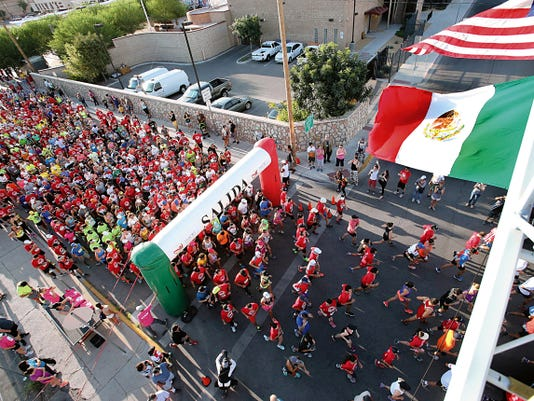 With the flags of the U.S. and Mexico flying from El Paso Fire Department Ladder 1, about 1,000 runners start the U.S.-Mexico 10K run at the foot of the Stanton Street bridge in El Paso on Saturday.
