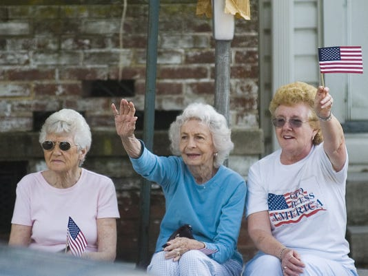 Hanover residents, from left, Mary Moore, Gloria Diehl, and Nancy King, wave to veterans as they ride by in cars in the Hanover Memorial Day Parade as it moved down Baltimore Street in 2011.