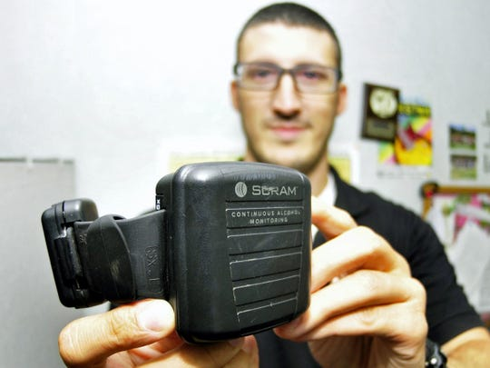 Probation officer Dan Signore displays an electronic alcohol monitoring system called SCRAM on Thursday, July 2, 2015 at Franklin County Adult Probation, 440 Walker Road, Chambersburg.