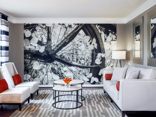 An oversized photo of a bicycle wheel 'wows' the eye when paired with circular double coffee tables, a tire-tread effect rug and window panels with sepia tones that match the mural.