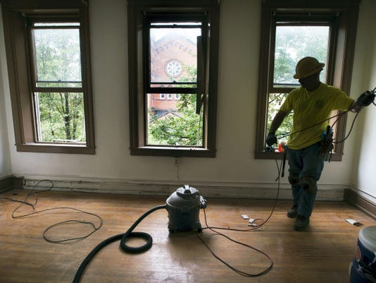Tony Jacquez, of York, coils up a vacuum after removing electric baseboard in an apartment Royal Square Development and Construction is rehabbing at 31 S. Duke St. in York. The building, which will have six apartments, will receive a new heating, ventilation and air conditioning system.