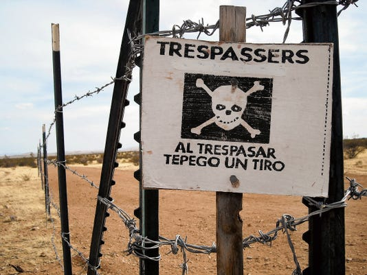 """Courtesy Photo   A stern warning for those who trespass along a border fence translates: """"If you trespass, I will shoot."""""""