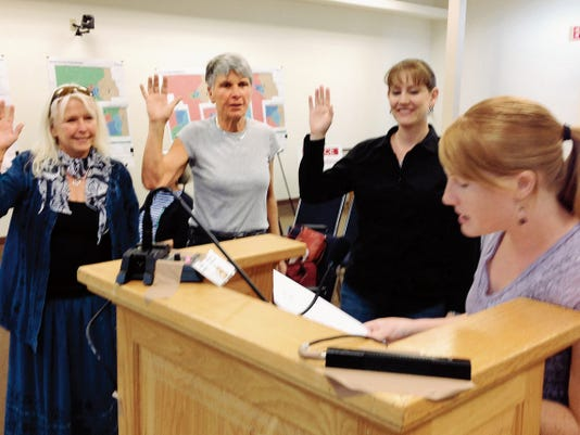 Debra St. Claire, owner of St. Claire's Organics, from left, Janey Katz, property owner, and Jaime Embick, planner/zoning administrator, are sworn in by Erin Johnson, at right, secretary of the Community Development Department on Tuesday during the Planning and Zoning Commission public hearing. Randal Seyler - Sun-News