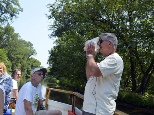Tour narrator Jim Schucker demonstrates the signaling technique used by canal boat captains with a drilled-out conk shell.