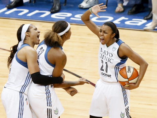 Minnesota Lynx players, from left, Maya Moore, Rebekkah Brunson and Renee Montgomery (21) celebrate in the second half of Game 5 of the WNBA finals against the Indiana Fever on Wednesday in Minneapolis.