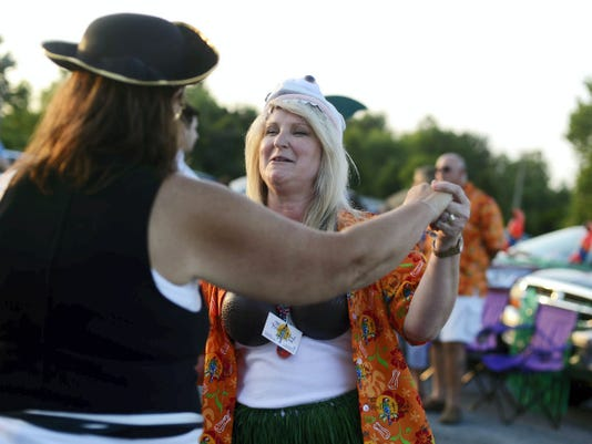 Dorothy Trostle of York Springs, left, dances with Debbie Zartman of Mechanicsburg before the simulcast of a Jimmy Buffett concert in Texas on the big screen at Haar's Drive-In Theater in Dillsburg Thursday. Both are members of the Hanover Area Parrot Head Society, a group that raises money for charity.