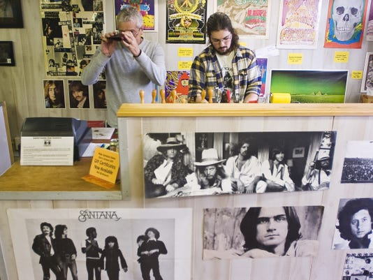 Owner Bob Smith, left, makes and sells leather belts, bags and accessories at Subterranean Soul, and sells T-shirts and classic rock records.