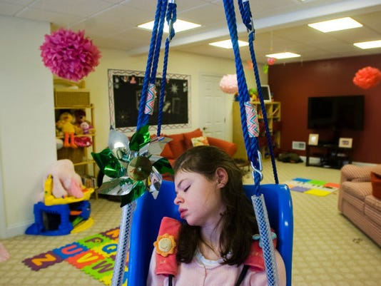 Lili Gilmore, 12, who has a rare form of epilepsy called Lennox Gestault syndrome, sleeps in her swing on Monday Jan. 27. Lili's daily routine might involve bursts of activity followed by exhaustion.