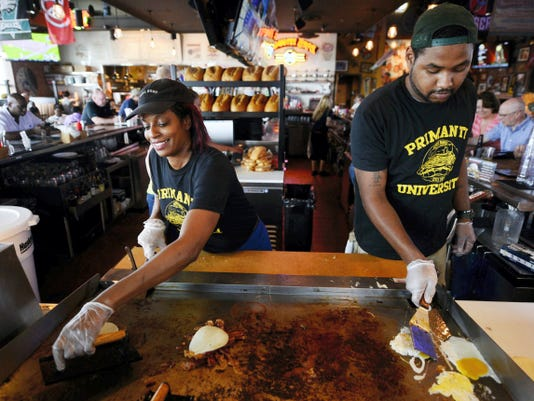 Jody Casey, left, and Damion Boyd work the grill at the bar at Primanti Bros. in York Township May 29.