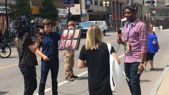 Colin Jost, holding the board, and Michael Che, right, are filming a segment for their 'Weekend Update' special in Cleveland.