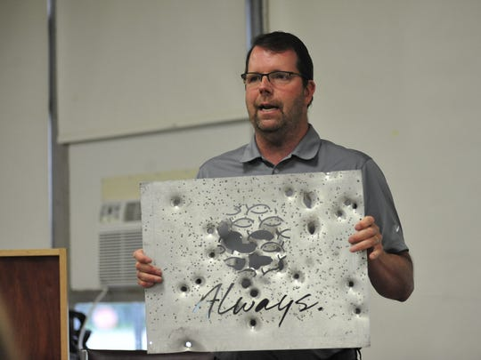 Rob Couturier holds an aluminum-alloy plate that would protect glass doors. This plate has been tested by law enforcement.