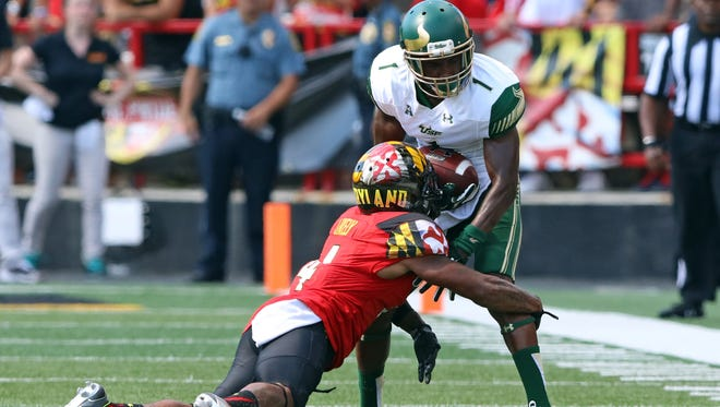 Maryland defensive back Will Likely (4) tackles South Florida wide receiver Chris Barr (1) after his catch at Byrd Stadium on Sept. 19, 2015.