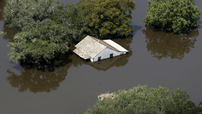 A home is surrounded by water from the flooded Colorado River in the aftermath of Hurricane Harvey Friday, Sept. 1, 2017, near Wharton, Texas.