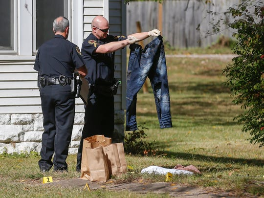 Police investigate the scene of a shooting as emergency