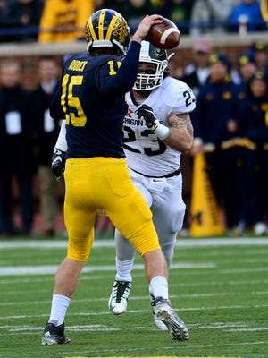 Michigan quarterback Jake Rudock (15) gets a pass off under pressure from MSU's Chris Frey (23) in the second quarter at Michigan Stadium, October 17, 2015 in Ann Arbor, Michigan.