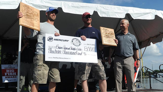 Chris Pickhardt and Brian Arneson, of Fond du Lac, hold up plaques and a check for $13,000 Sunday afternoon, for winning the Mercury Marine, Walleye Weekend fishing tournament. Sunday June 14, 2015