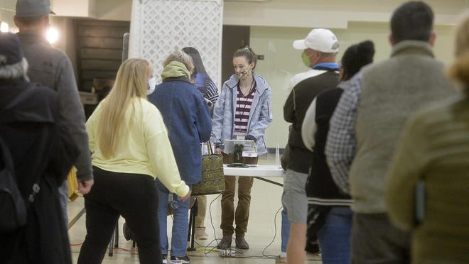 Voters line up to show their ID at Windsor Forest Baptist Church before casting their ballot.