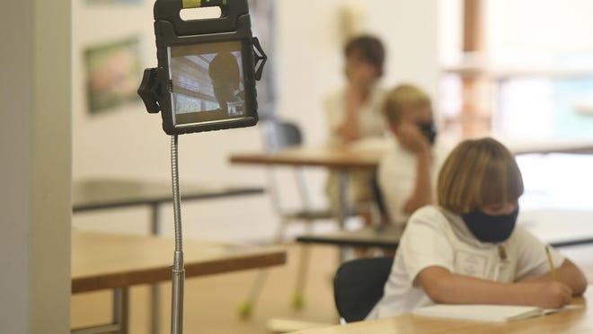 A student virtually attends class using a tablet on the first day of the 2020-2021 school year at Tuesday Brunswick's Lower School in Greenwich, Conn.