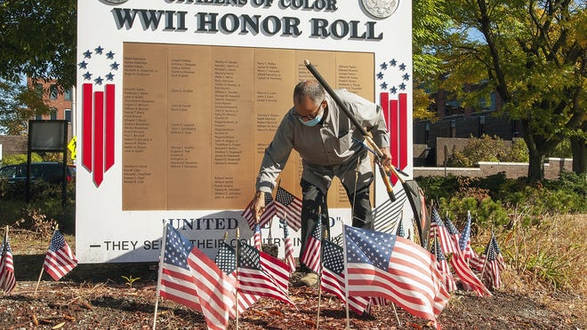 Bill Coleman straightens American flags in front of the Citizens of Color WWII Honor Roll in Worcester's Lincoln Square on Wednesday as he does his regular cleanup of the area.