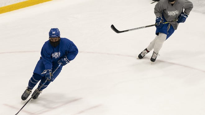 The Becker College men's hockey team wear masks underneath their helmets during practice at the Worcester Ice Center on Friday. While youth hockey has been put on pause within the state due to increasing COVID-19 cases linked to rinks, college and pro teams are still allowed to practice.