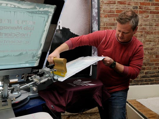 Jerrod Myers, director at Big Ideas Branding and Apparel, checks a shirt Thursday at Big Ideas Branding and Apparel in downtown Lancaster. Myers said he had interest in the Bicycle Corner property but would also like to see new businesses grow in downtown Lancaster.