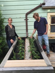 Carrie Bristol-Groll (left), principal civil engineer with Stormwater Solutions Engineering LLC of Milwaukee, shows a StormGUARDen she designed for small urban lots. This one is installed in the backyard of the N. Pierce St. home owned by Harlan Groll (right).