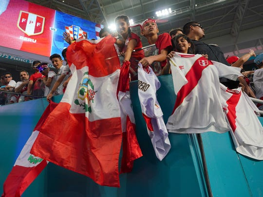 Fans of the Peruvian national team waive flags prior