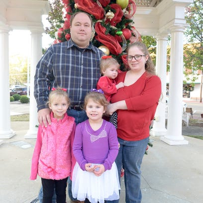 Blake and Stephanie Gilbert stand with their daughters,