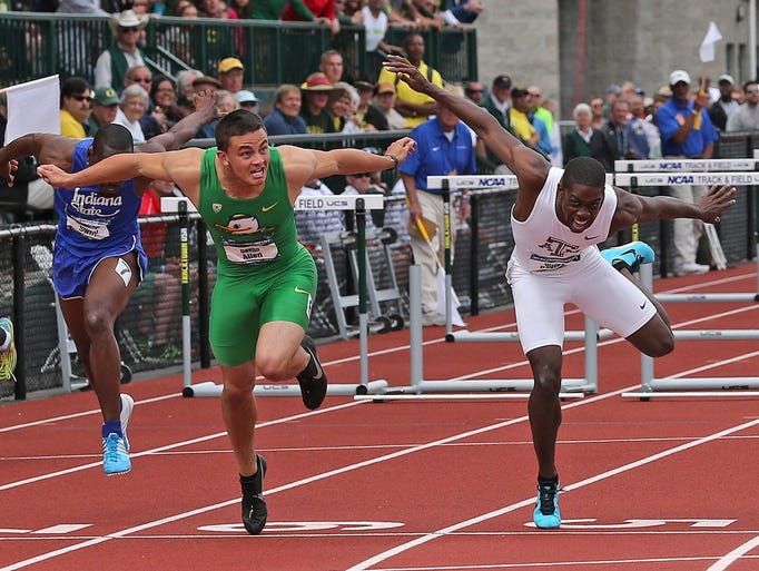 Oregon's Devon Allen reaches for the finish line during the men's 110-meter hurdles at the NCAA track and field championships on Saturday, June 14, 2014, in Eugene, Ore.
