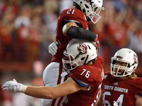 USD's Trevor Bouma (21) is picked up by teammate Nick Jensen (76) after scoring a touchdown against UNI on Saturday at the DakotaDome in Vermillion.