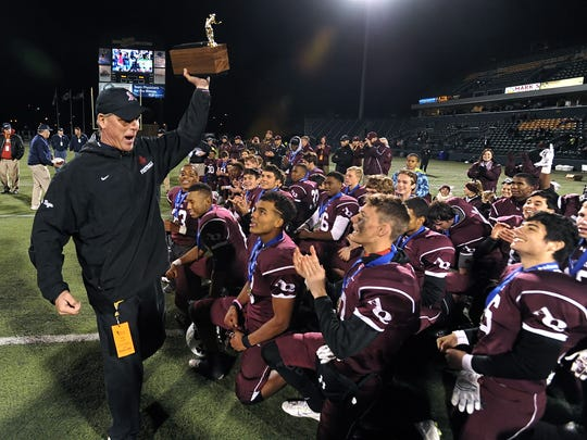 Aquinas head coach Chris Battaglia brings the Section V Class AA championship trophy to his players after the 2015 final at Sahlen's Stadium.