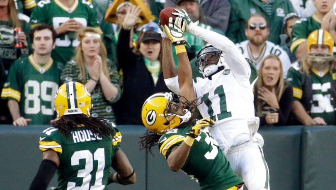 New York Jets receiver Jeremy Kerley (11) catches a ball in the end zone over Green Bay Packers cornerback Tramon Williams on a play that was called back because a timeout was signaled before the snap during the second half of Sunday's game at Lambeau Field.