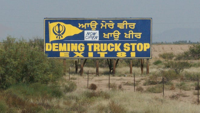 A billboard west of town advertising the Deming Truck Terminal features a Punjabi expression and an emblem of the Sikh faith, aimed at Indian- and Pakistani-born truck drivers.