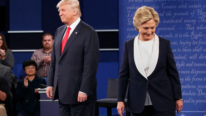 Donald Trump and Hillary Clinton walk to their seats after arriving for the second presidential debate at Washington University.