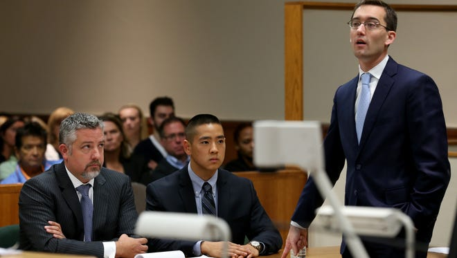 Brian DeCarolis points to his client Charles Tan during opening remarks in his murder case.